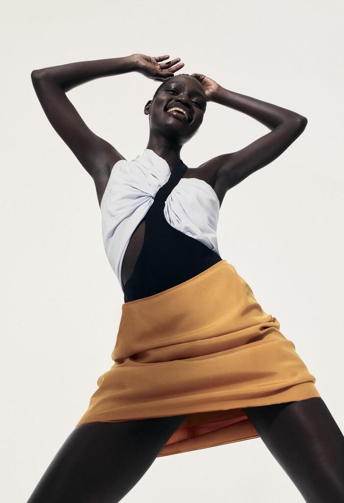 Modellen har på sig en svartvit body och en gul kjol
