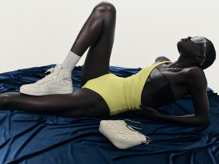 Modellen har på sig en gul baddräkt, svart bandeau topp och vita sneakers